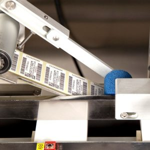 Наклеивание этикетки с серийным номером и штрих кодом на картонную упаковку лекарств
